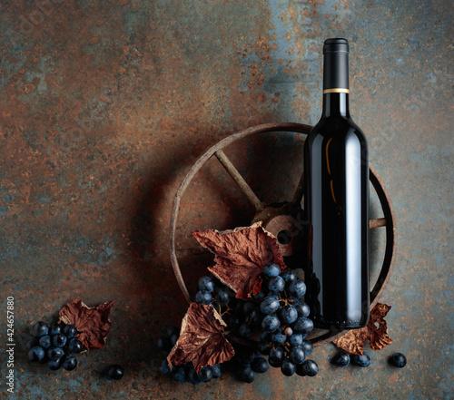 Fototapeta Bottle of red wine with an old rusty wheel. obraz na płótnie