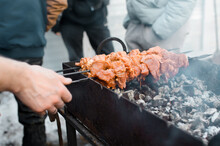 Man Cooking Barbecue On Coals Outside, Close-up. Male Hand Twists The Skewers. Picnic Concept, Outdoor Party, Kebab Season Opening