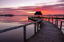 Pier Construction And Shelter With Thatched Roof At Beautiful Red Sunrise Under Cloudy Sky At Lake Hemmelsdorf, Schleswig-Holstein, Northern Germany