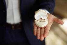 The Man The Groom In A White Shirt And Blue Jacket Holds On His Palm Wedding Gold Rings In A Red Velvet Box By The Window. Groom Morning, Close-up Without A Face Only Hands