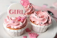 Delicious Cupcakes With Pink Cream And Toppers For Baby Shower On Plate, Closeup