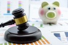 Legal Office Of Lawyers, Justice And Law Concept : Wooden Judge Gavel Or A Wood Hammer And A Soundboard Used By A Judge Person On A Desk With A Blurred Piggy Bank Behind.
