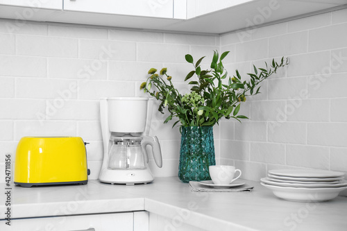 Fotografering Modern yellow toaster, coffeemaker and dishware on countertop in kitchen