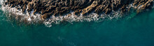 The Ocean's Wave Hitting Rocks. Blue Water Background. Aerial View. The Natural Landscape. Wallpaper. Ocean Concept.