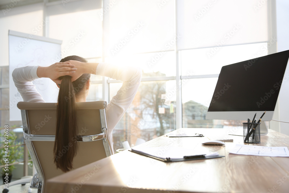 Fototapeta Young woman relaxing in office chair at workplace, back view