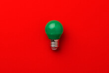 One Light Bulb On Red Background Top View