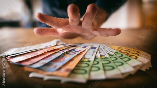 Valokuva Hand greift nach Euro-Banknoten