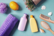 Flat Lay Photography Hair Care Cosmetic Products. Purple Shampoo Bottle, Orange Conditioner Packaging, Wooden Comb, Flowers, Towel