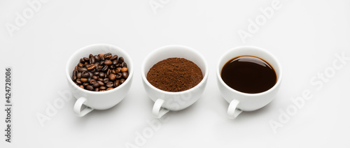 Foto cups with prepared and ground coffee near beans on white, banner