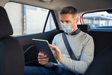 Man Sitting In Taxi With Face Mask Using Digital Tablet