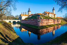 View Of Historic Fortified Nesvizh Castle, Landscape Park And Ponds On Sunny Winter Day, Belarus