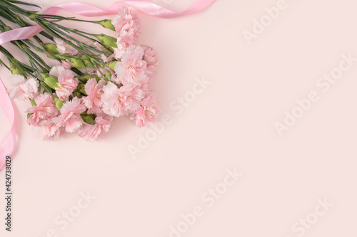 Fotografia Design concept of Mother's day holiday greeting with carnation bouquet on pink t