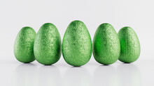 Easter Eggs Isolated Against A White Background. Chocolate Eggs Wrapped In  Green Foil. 3D Render