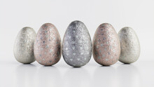 Easter Eggs Isolated Against A White Background. Chocolate Eggs Wrapped In Patterned Silver Foil. 3D Render