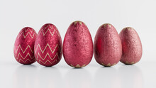 Easter Eggs Isolated Against A White Background. Chocolate Eggs Wrapped In Patterned Rose Gold And Red Foil. 3D Render