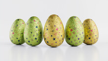Easter Eggs Isolated Against A White Background. Chocolate Eggs Wrapped In Patterned Yellow, Green And Purple Foil. 3D Render