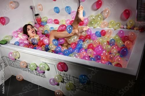 Belle femme qui s'amuse dans un bain de ballons Fotobehang