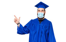 Photo Of Student Man In Bachelor Clothes And Graduating Cap Pointing Away While Wearing Facial Mask