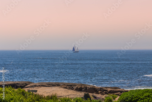 Fotografiet A sailing boat can be seen from a beachside in Maine USA