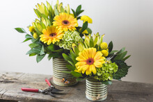Yellow Daisy Flower Arrangements In Metal Tin Containers On A Rustic Wood Garden Bench With Pruners