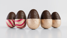 Easter Eggs Isolated Against A White Background. Partially Unwrapped Chocolate Eggs With Patterned Rose Gold And Red Foil. 3D Render