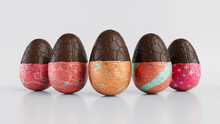 Easter Eggs Isolated Against A White Background. Partially Unwrapped Chocolate Eggs With Patterned Orange, Red And Silver Foil. 3D Render