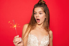 Pyrotechnics And People Concept - Smiling Young Woman Or Teenage Girl Happy Woman With Sparklers Celebrate In White Dress On Red Background. Surprised