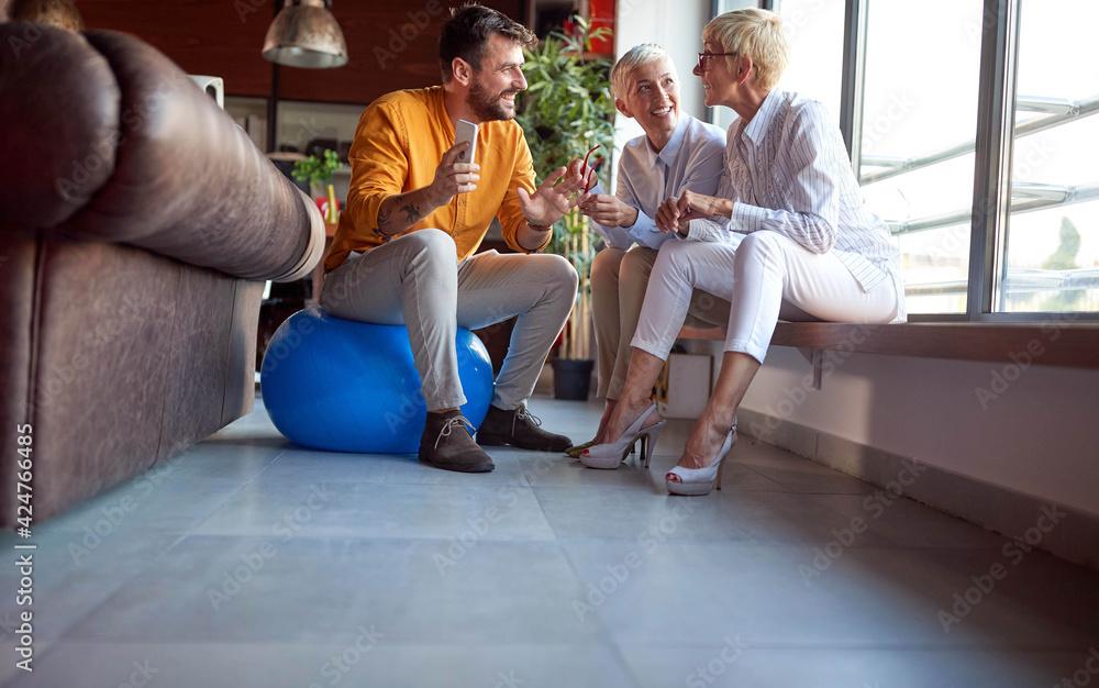 Fototapeta Group of jolly colleagues socialazing on a break