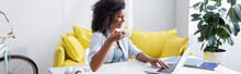 Smiling African American Woman With Cup Of Coffee Using Laptop At Home, Banner
