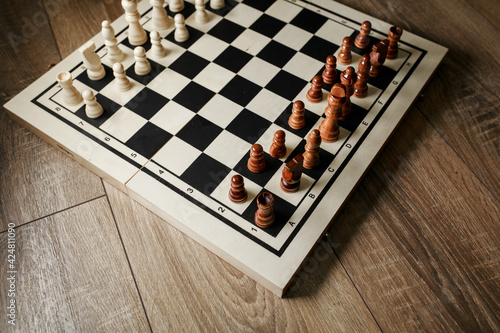 Fototapeta Chess board with chess on a parquet background.