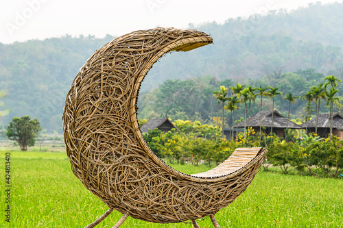 Fotografie, Obraz A bench made of half-moon rattan in a green paddy field with a mountain backdrop and a village
