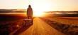 canvas print picture - Junge Frau mit einem Koffer bei Sonnenuntergang