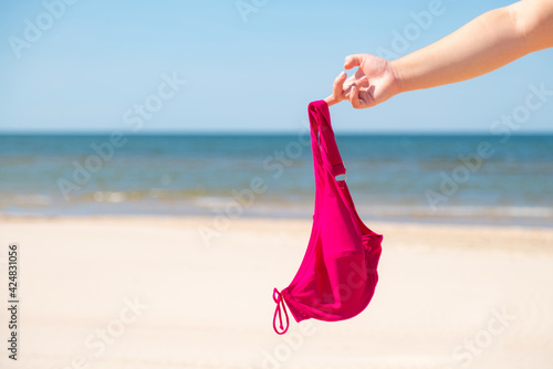 Fotografie, Obraz Close up of young woman taking off her bra at nude beach