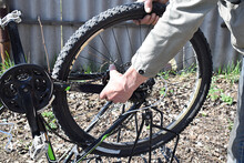 A Man Dismantles The Rear Wheel Of A Bicycle.