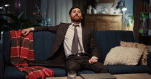 Tired Young Businessman Returning Home Removing Suit Tie Relaxing On The Sofa. Living Room Apartment. Corporate Person ;lifestyle. Workaholic.