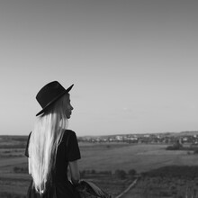 Black And White Portrait, Back View Of Young Girl In Black Dress Wearing Hat On Sky Background.