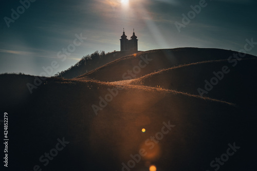 silhouette of Calvary church in Banska Stiavnica, Slovakia. Sunset light
