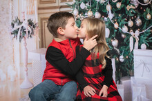 Siblings In Front Of A Christmas Tree