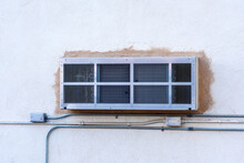 New Packaged Terminal Air Conditioner Unit Covered With Rear Grille Installed Through A Commercial Building Exterior Wall. Electrical Conduit Pipes And Boxes On Unpainted Wall Surface