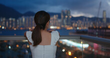 Woman Look At The City From Balcony At Night