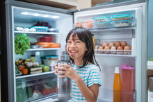 Thirsty Happy Young Asian Girl Open Fridge Door Drinking A Bottle Of Water
