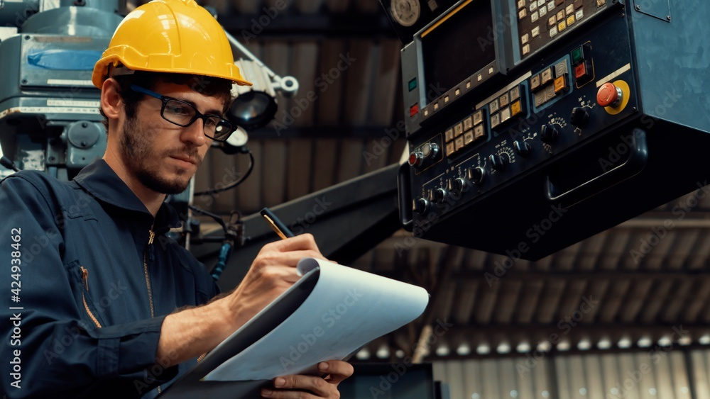 Fototapeta Skillful factory worker working with clipboard to do job procedure checklist . Factory production line occupation quality control concept .