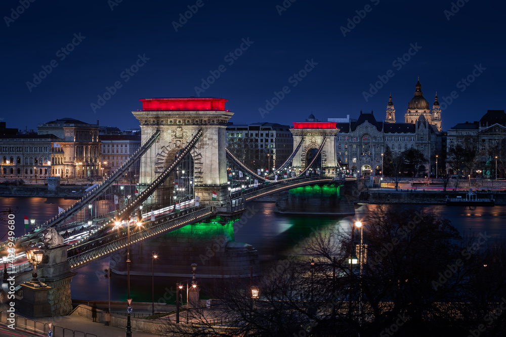 Fototapeta Budapest, Hungary - The world famous illuminated Szechenyi Chain Bridge (Lanchid) by night, lit up with national red, white and green colors, celebrating the 15th of March 1848 civic revolution day