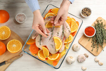 Woman Adding Thyme To Raw Chicken With Orange Slices At White Wooden Table, Top View