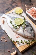 Fresh Raw Dorado Fish. Dorado Fish And Cooking Ingredients - Lime, Salt, Oil, Garlic, Thyme And Herbs.
