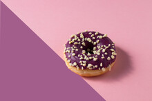 Donut With Blueberry Glaze And Nuts  On Two Colour Background .Sweet Minimalist Food Image. Modern Concept.