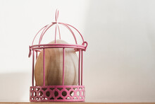 A Wooden Egg In A Pink Cage On A Light Background.