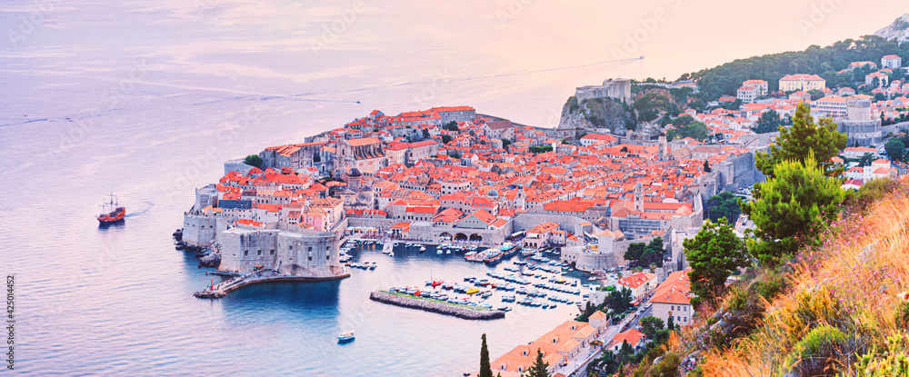 Fototapeta Panoramic top view of the Old Town of Dubrovnik, banner, panorama in beautiful evening light at sunset, the Adriatic coast of Croatia