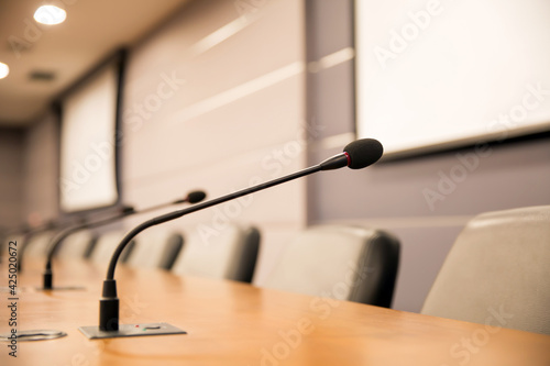 Foto Close up the conference microphone on the meeting table or board room for speake