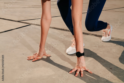 Billede på lærred elegant sportive girl wearing headphones prepare to run close up